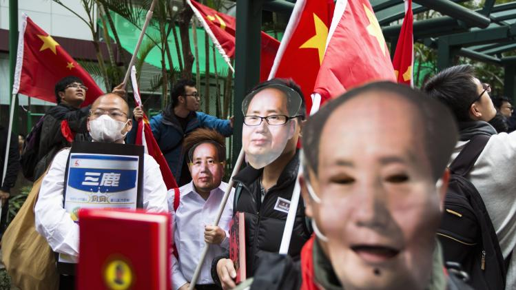 Protesters wear masks of late Chinese Communist Party leader Mao during a anti-mainland tourist rally in Hong Kong's famous Mong Kok shopping district