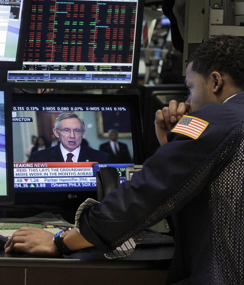 A specialist watches Sen. Harry Reid as he works on the floor of the New York Stock Exchange Monday, Aug. 1, 2011. (AP Photo/Richard Drew)