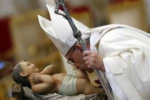 Pope Francis kisses a baby Jesus statue as he leads …