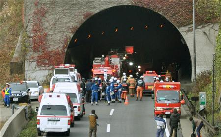 Police officers and firefighters gather in front of the Sasago Tunnel on the Chuo Expressway in Otsuki