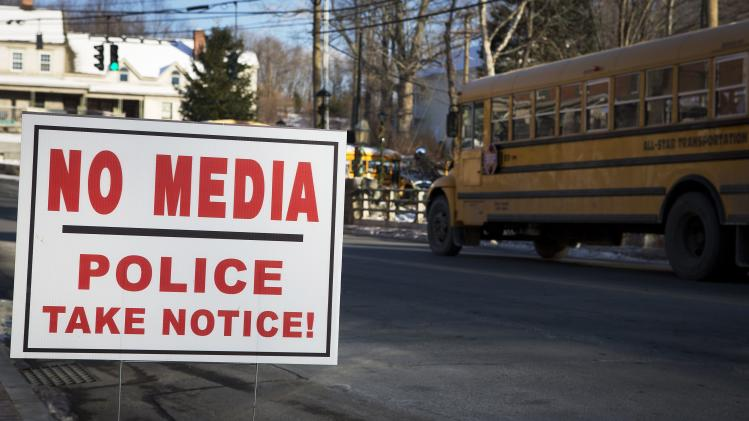 A sign is pictured as a school bus drives past in the Sandy Hook area of Newtown, Connecticut