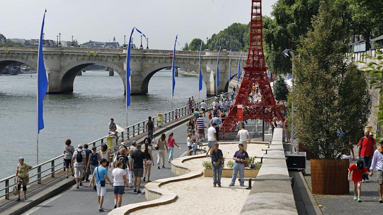 Tourists and Parisians take advantage of the Paris Plage event, an artificial beach set up on the right bank of the Seine river in Paris, with palm trees, outdoor showers and hammocks, Wednesday, July 23, 2014. Paris Plage, the artificial seaside stretching along the Seine has kept Parisians cool each summer since 2001. The event lasts until August 17. Visible at right is a model of the Eiffel Tower made with garden chairs. (AP Photo/Remy de la Mauviniere)