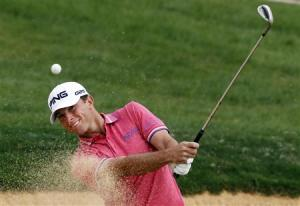 Luke Guthrie of U.S. hits out of a sand trap on the 7th hole during the BMW Masters 2013 golf tournament at Lake Malaren Golf Club in Shanghai