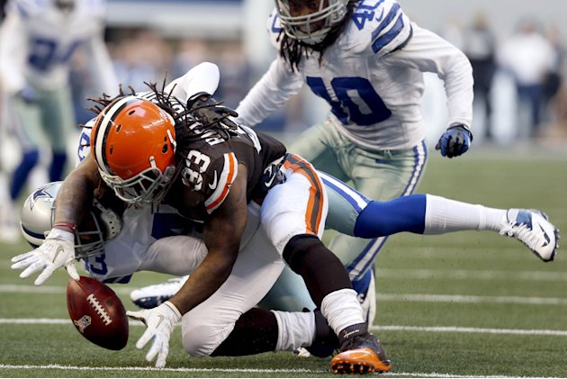 Cleveland Browns running back Trent Richardson (33) loses control of the ball after being tackled by Dallas Cowboys' Gerald Sensabaugh (43) as Danny McCray (40) watches in the second half of an NFL fo