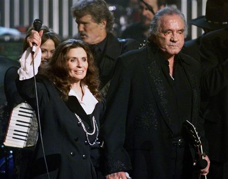 Country music singer-songwriter Johnny Cash and his wife June Carter Cash wave to fans at the end of a tribute in his honor in New York