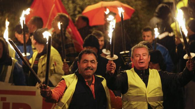 Night shift workers of the Ford car factory in the Cologne suburb of Niehl, hold flaming torches during a temporary walkout for higher wages by Germany's engineering and metal workers union IG Metall