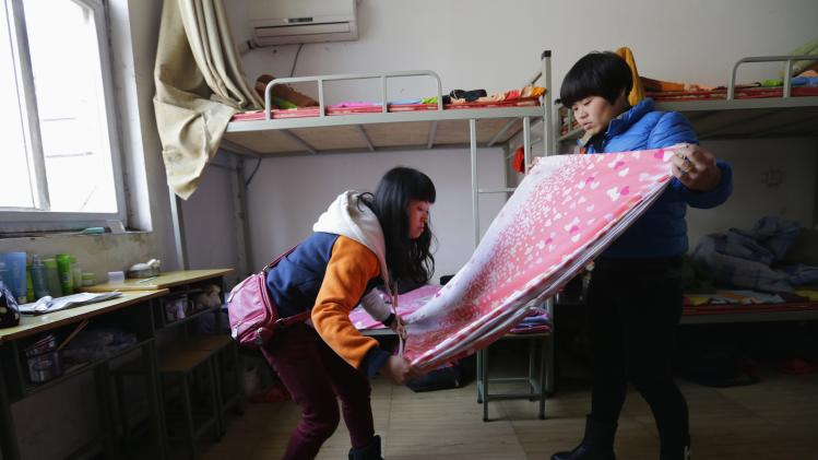 Wang Feng folds a sheet, as she packs after finishing her training and being assigned to work at a Liangtse Wangjing store in Beijing, at Huaxia Liangtse Massage Training Center in Zhengzhou, Henan province