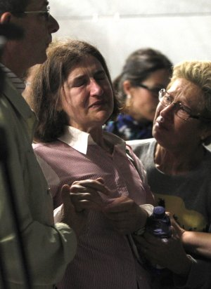 A woman reacts as relatives of victims of a train accident…