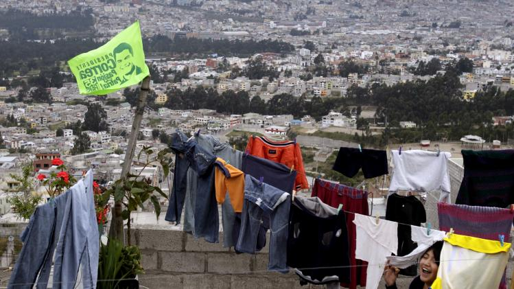 In this Jan. 28, 2013 photo, a girl plays on the terrace of her home where clothes dry where an election campaign flag flies in support of the reelection of President Rafael Correa in Quito, Ecuador. Correa is running for reelection on Sunday, Feb. 17. (AP Photo/Dolores Ochoa)