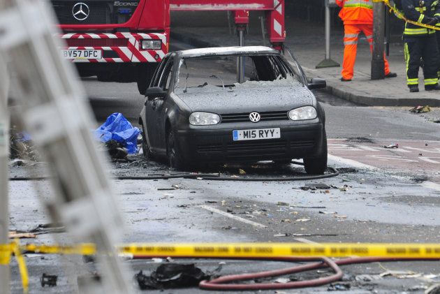 A damaged car remains in the street after a helicopter crashed into a construction crane on top of St George's Wharf tower building, in London, Wednesday Jan. 16, 2013. Police say two people were kill