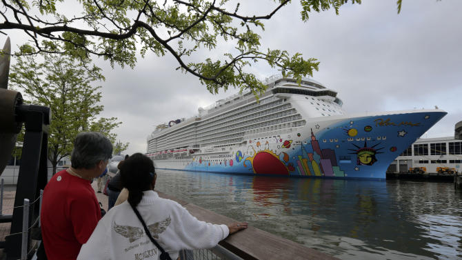 People pause to look at the Norwegian Cruise Line's new ship, Norwegian Breakaway, which was christened at a pier on the Hudson River, in New York, Wednesday, May 8, 2013. The ship has a colorful mural on the exterior hull design by pop artist Peter Max featuring the city skyline and the Statue of Liberty. (AP Photo/Richard Drew)