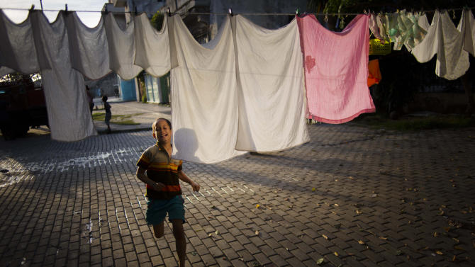 A youth runs past a clothes line as he plays with neighborhood kids in Havana, Cuba, Saturday, Dec. 27, 2014. Cuba and the U.S. announced on Dec. 17 that the two countries would resume diplomatic relations for the first time since 1961. (AP Photo/Ramon Espinosa)