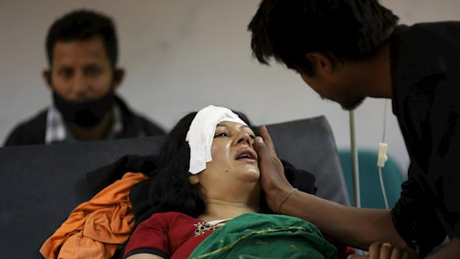 Boy comforts his mother who was injured during an earthquake, at a trauma center in Kathmandu