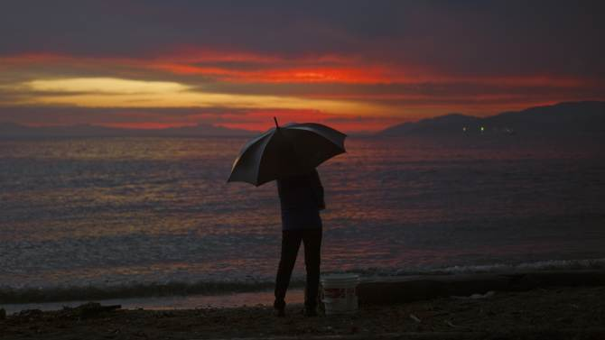 Woman stands in the rain at sunset along the shoreline in West Vancouver, British Columbia