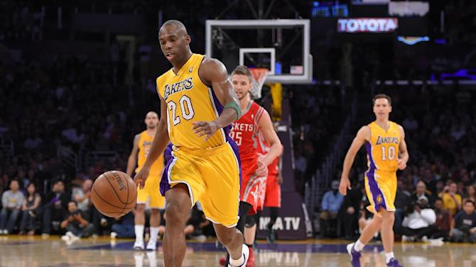 Los Angeles Lakers guard Jodie Meeks, left, takes a pass from guard Steve Nash, right, as forward Houston Rockets forward Chandler Parsons watches during the first half of an NBA basketball game, Tuesday, April 8, 2014, in Los Angeles. With that assist, Nash took sole possession of third place for NBA all-time assists