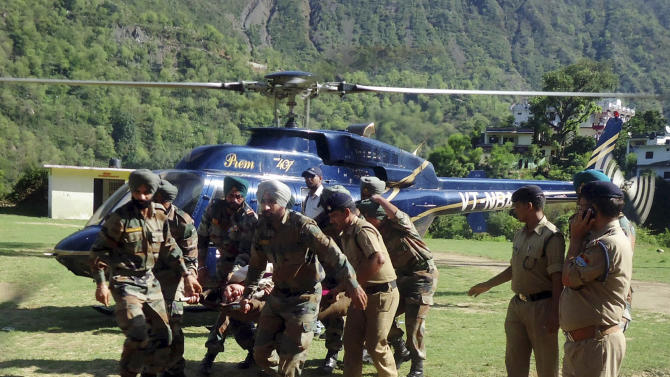 Indian army personnel carry an injured flood victim on a stretcher for treatment in Hemkund, in the northern Indian state of Uttarakhand, India, Wednesday, June 19, 2013. A joint army and air force operation has evacuated nearly 12,000 Hindu pilgrims stranded in a mountainous area by torrential monsoon rains and landslides in northern India, but nearly 63,000 people remain cut off, a senior official said Wednesday. (AP Photo)