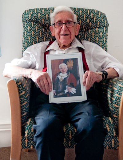 This undated handout image issued by Gracewell Healthcare on Friday, June 6, 2014, of Bernard Jordan an 89-year-old veteran, holding a picture of himself as the Mayor of Hove from 1995 to 1996. An 89-year old World War II veteran who was reported missing from a nursing home in England has been found in Normandy after traveling to attend D-Day commemorations, police said Friday. Bernard Jordan was last seen at The Pines home in Hove, southern England, on Thursday morning. Staff called police when he did not return that evening. (AP Photo/Gracewell Healthcare/PA)