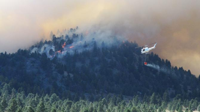 A helicopter heads toward a burning ridge on Monday, June 25, 2012, north of Helena, Mont. Scorching heat and high winds caused wildfires to break out across southwestern Montana, forcing the evacuation of more than 200 homes. (AP Photo/Matt Volz)