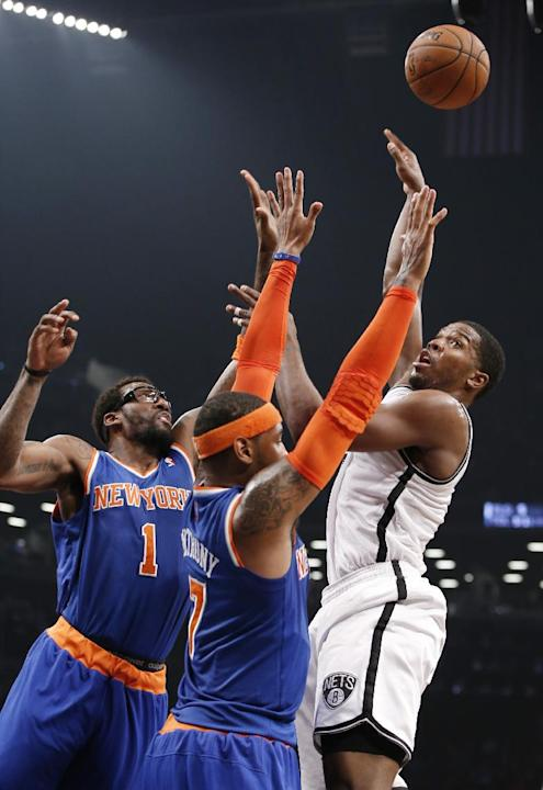 Brooklyn Nets shooting guard Joe Johnson (7) shoots over as New York Knicks forward Amar'e Stoudemire (1) and New York Knicks forward Carmelo Anthony (7) defend in the first half of their NBA bask