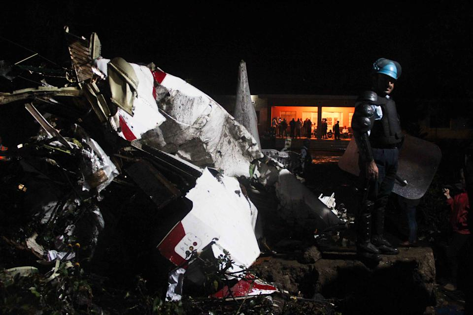 A United Nations peacekeeper stands beside the wreckage of a plane that crashed in Goma, Congo Monday, March 4, 2013. A Fokker airplane of the private airline CAA crashed in the city center Monday, killing at least six people onboard. There were no reported casualties on the ground.(AP Photo/Melanie Gouby)