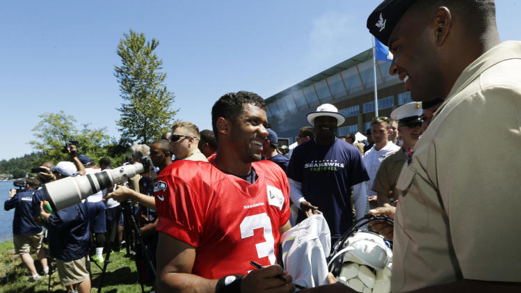 Seattle Seahawks quarterback Russell Wilson signs autographs for members of the military attending NFL football training camp, Thursday, July 31, 2014, in Renton, Wash. (AP Photo/Ted S. Warren)