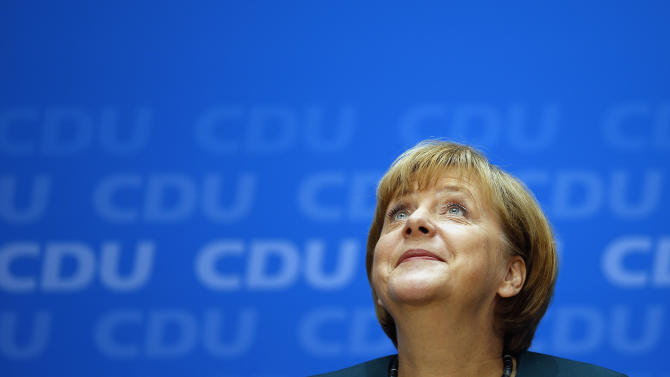German Chancellor and chairwoman of the German Cristian Democratic party (CDU), Angela Merkel looks up during a press conference after a party's board meeting in Berlin, Monday, Sept. 23, 2013. German Chancellor Angela Merkel may have won an impressive third general election but she faces a delicate and lengthy task in forming a new government as party leaders met Monday to map out their next steps. Merkel's Union bloc achieved its best result in 23 years Sunday to put her on course for a third term, winning 41.5 percent of the vote and finishing only five seats short of an absolute majority in the lower house. However, Merkel's pro-business coalition partner since 2009 crashed out of Parliament. (AP Photo/ Michael Sohn)