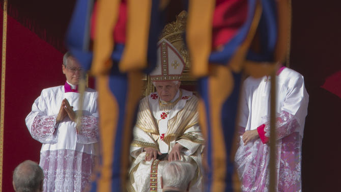 Pope Benedict XVI is framed by a Swiss Guard as he celebrates a canonization ceremony, in St. Peter's Square, at the Vatican, Sunday, Oct. 21, 2012. The pontiff will canonize seven people, Kateri Tekakwitha, Maria del Carmen, Pedro Calungsod, Jacques Berthieu, Giovanni Battista Piamarta, Mother Marianne Cope, and Anna Shaeffer. (AP Photo/Andrew Medichini)