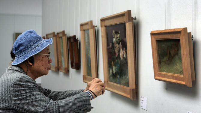 """In this photo taken May 8, 2008, a man moves close to take a photo of the early 1887 painting """"Nude Woman Reclining"""" by Vincent van Gogh at Kroeller-Mueller museum, Otterlo, eastern Netherlands. With the Van Gogh Museum in Amsterdam closed for renovations, the world's second-largest collection of the tortured Dutch master's work is stepping into the limelight. The lesser-known Kroeller-Mueller museum in the eastern Netherlands has revamped the layout of its central rooms, giving more space and focus to many of its top works. (AP Photo/Peter Dejong)"""