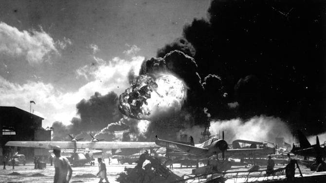 FILE - In this Dec. 7, 1941 photo provided by the U.S. Navy, sailors stand among wrecked airplanes at Ford Island Naval Air Station as they watch the explosion of the USS Shaw in the background, during the Japanese surprise attack on Pearl Harbor, Hawaii. (AP Photo)