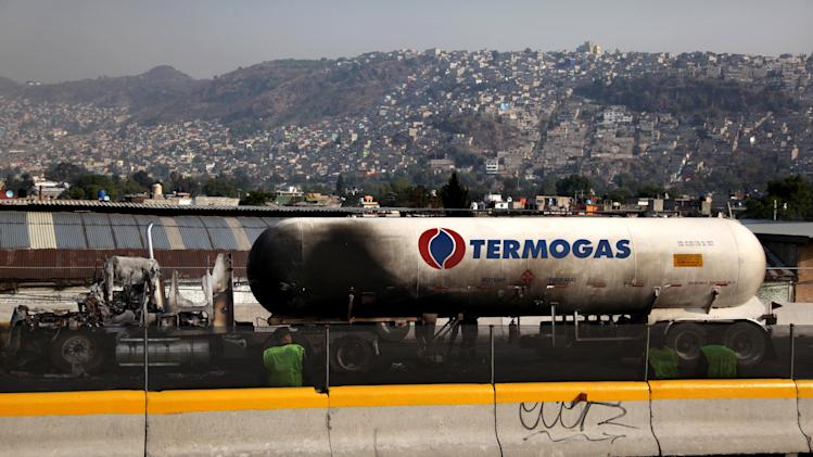 The remains of a gas tanker sits on a highway in the Mexico City suburb of Ecatepec, after it exploded early Tuesday, May 7, 2013. The blast killed and injured dozens, according to the Citizen Safety Department of Mexico State. Officials did not rule out the possibility the death toll could rise as emergency workers continued sifting through the charred remains of vehicles and homes built near the highway on the northern edge of the metropolis. (AP Photo/Marco Ugarte)