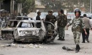 Members of the Egyptian Army keep guard near burnt vehicles in front of a police station, which was stormed into and set on fire by protesters, in the city of Suez in this January 28, 2013 file picture. To match Insight EGYPT-ARMY/ REUTERS/Stringer/Files (EGYPT - Tags: POLITICS CIVIL UNREST MILITARY)