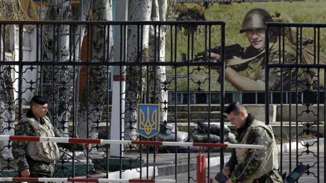 Ukrainian soldiers stand guard at the gate of a military base in the port of Kerch, Ukraine, Monday, March 3, 2014. Pro-Russian troops controlled a ferry terminal on the easternmost tip of Ukraine's Crimea region close to Russia on Monday, intensifying fears that Moscow will send even more troops into the strategic Black Sea region in its tense dispute with its Slavic neighbor. (AP Photo/Darko Vojinovic)