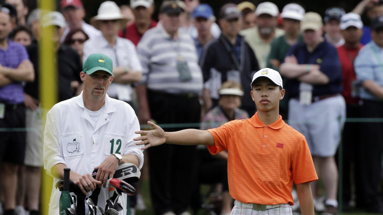 Amateur Guan Tianlang, of China, talks to his Brian Tam on the first green during the second round of the Masters golf tournament Friday, April 12, 2013, in Augusta, Ga. (AP Photo/David J. Phillip)