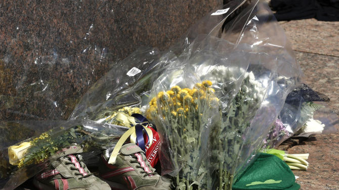 A makeshift memorial including a pair of running shoes sits on the campus of Boston University after it was learned that BU student Lu Lingzi was one of the victims of the Boston Marathon bombings in Boston Wednesday, April 17, 2013. (AP Photo/Winslow Townson)