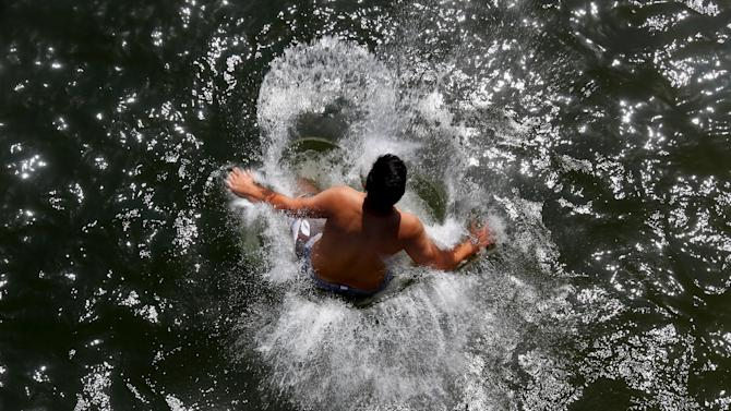 A man jumps into the cool waters of the Ammersee lake in Utting