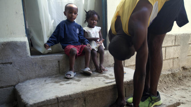 In this Jan. 8, 2013 photo, Astrel Clovis, a 42-year-old marathon runner, stretches his leg muscles outside his home as two of his young neighbors watch, in Petionville, a suburb of Port-au-Prince, Haiti.  Like virtually all Haitians in the capital of 3 million, the runner's life was disrupted by the catastrophic earthquake on Jan. 12, 2010.  Before the quake, he shared a three-bedroom house with his aunt and cousins, and dreamed of running his first marathon. The quake destroyed that house, along with about 100,000 homes across the capital and southern Haiti. The government put the death toll at 316,000, but no one knows how many people died. Clovis was lucky. He didn't lose any relatives, or close friends  - or his marathon dreams. (AP Photo/Dieu Nalio Chery)