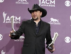 Jason Aldean poses with his awards for male vocalist of the year and vocal event of the year backstage at the 48th ACM Awards in Las Vegas