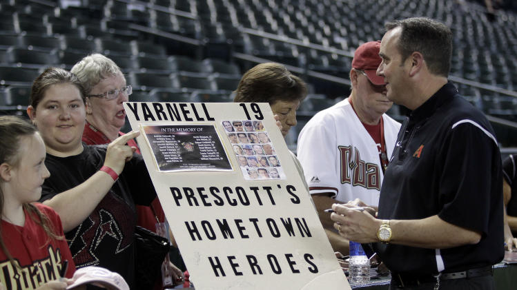 Arizona Diamondbacks President & CEO Derrick Hall, right, acknowledges the Prescott Fire Department and fans before a game between the Arizona Diamondbacks and Colorado Rockies on Friday, July 5, 2013, in Phoenix. Prescott lost 19 fire fighters during a fire in Yarnell. (AP Photo/Rick Scuteri)