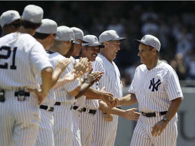Former New York Yankees players, including Ron Guidry, third from right, and former Yankees pitching coach Mel Stottlemyre greet former New York Yankees manager Joe Torre, right, during introductions