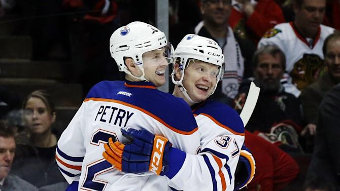 Edmonton Oilers defenseman Jeff Petry (2) celebrates with center Lennart Petrell, of Finland, after his goal during the first period of an NHL hockey game against the Chicago Blackhawks, Monday, Feb. 25, 2013, in Chicago. (AP Photo/Charles Rex Arbogast)