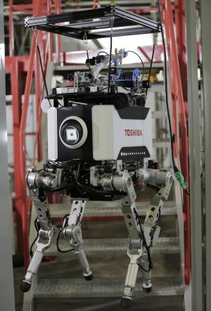 Toshiba Corp.'s nuclear inspection robot is set on stairs before climbing stairs during a demonstration at a Toshiba factory in Yokohama, west of Tokyo, Wednesday, Nov. 21, 2012. The four-legged robot is designed to help at the meltdown-crippled Japanese nuclear plant, climbing over debris and venturing into radiated areas off-limits to human workers. (AP Photo/Itsuo Inouye)