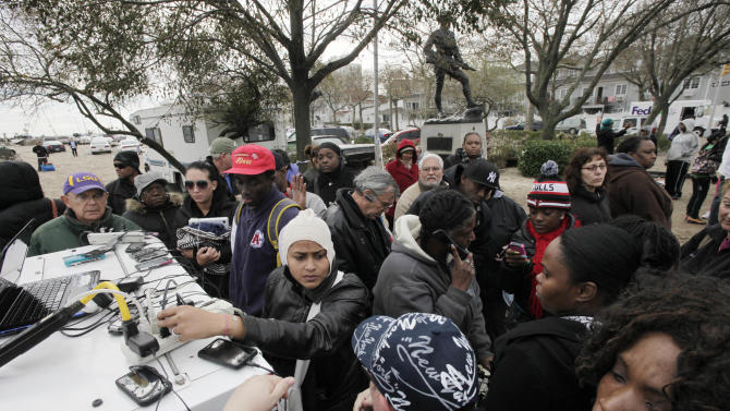 Residents of the oceanside community of Far Rockaway, New York, crowd around a portable generator to charge cell phones and laptops, Thursday, Nov. 1, 2012.    Hundreds of thousands in New York City alone were still without power Thursday, especially in Lower Manhattan, which remained in the dark roughly south of the Empire State Building after floodwaters had knocked out power. (AP Photo/Mark Lennihan)