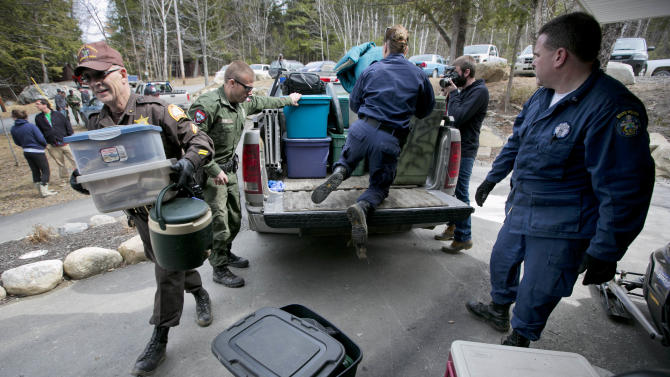 Law enforcement officials unload items removed from a camp used by Christopher Knight, Thursday, April 11, 2013, in Rome, Maine.  Knight, known as the North Pond Hermit, was arrested Thursday, April 4, 2013, while stealing food at a camp in Rome. Authorities said he may be responsible for more than 1,000 burglaries during his decades in the woods. (AP Photo/Robert F. Bukaty))