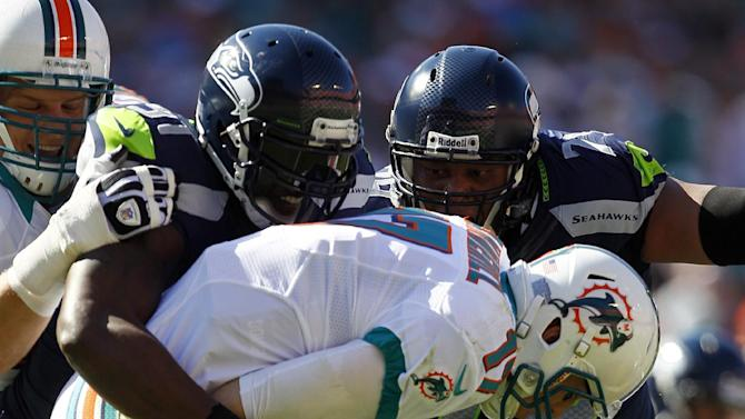 Seattle Seahawks defensive end Chris Clemons (91), left, and  Red Bryant (79) sack Miami Dolphins quarterback Ryan Tannehill (17) during the first half of an NFL football game on Sunday, Nov. 25, 2012, in Miami. (AP Photo/Gerry Broome)