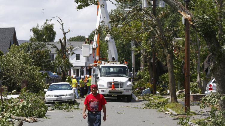 A man walks amid cleanup crews on Vinal Street in Revere