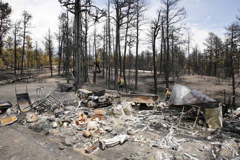Firefighters are pictured beyond a burned structure as they work hot spots on the Black Forest wildfire north of Colorado Springs, Colo., on Monday, June 17, 2013. Over 470 homes burned in the wildfire that started last Tuesday. (AP Photo/Ed Andrieski)