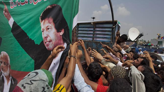 Supporters of Pakistani cricketer-turned-politician Imran Khan, shown in the banner, jostle to get food while in a rally in Islamabad, Pakistan, Aug. 22, 2014. Thousands of Imran Khan's and Tahir-ur-Qadri's supporters are besieging parliament in the capital to pressure Prime Minister Nawaz Sharif to resign over alleged election fraud. (AP Photo/B.K. Bangash)