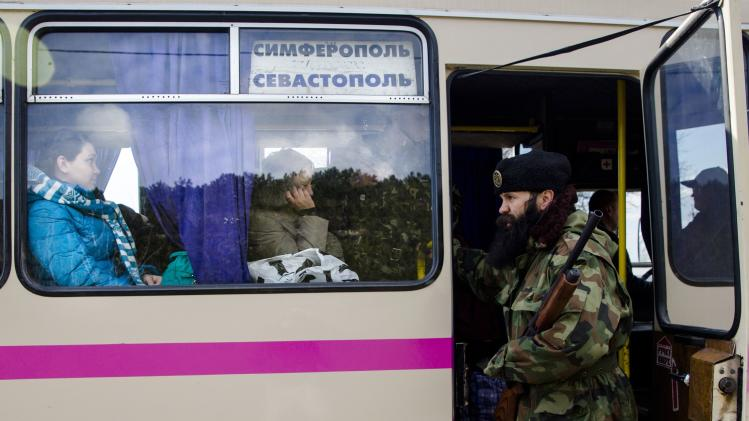 A member of a Serbian Chetnik paramilitary group checks a passenger bus at a checkpoint in the Crimean peninsular