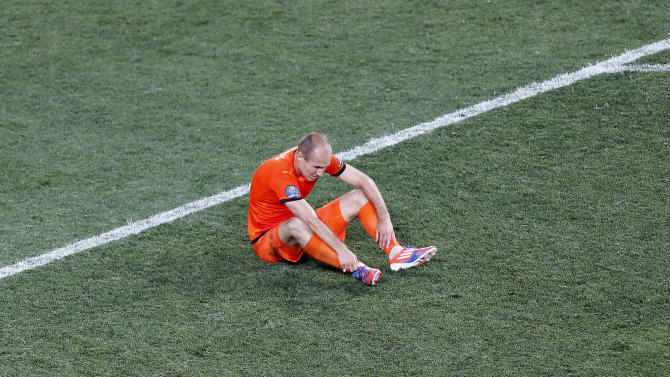 Arjen Robben from the Netherlands sits on the pitch at the end of the Euro 2012 soccer championship Group B match between the Netherlands and Denmark in Kharkiv , Ukraine, Saturday, June 9, 2012. Denmark won the match 1-0.  (AP Photo/Michael Probst)
