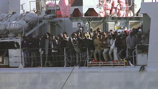 In this image from TV, migrants crowd at the rail aboard an Italian navy vessel as it cruises towards Italian port of Messina, Saturday April 18, 2015. UNHCR says Sunday, April 19, 2015, the search and recovery rescue operation is under way after a boat carrying migrants overturned north of Libya. (AP Photo/APTV)
